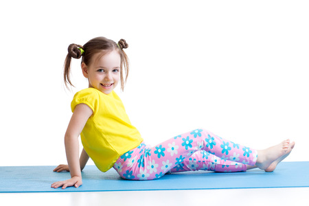 child girl doing gymnastics exercises on mat