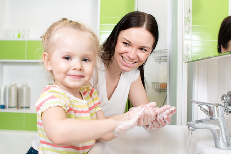 happy family - child and mother washing hands with soap in bathroom