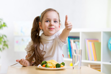 child girl eats healthy food showing thumb up