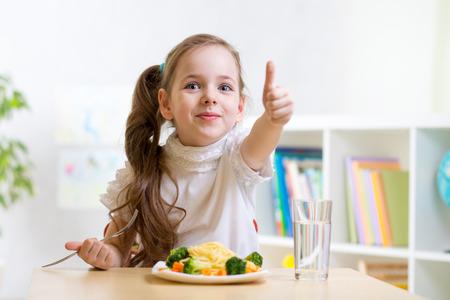 niños felices: Chica niño come alimentos saludables que muestra el pulgar arriba