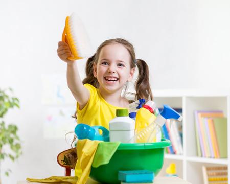 domestic chore: Joyful kid little girl cleanses a floor in nursery