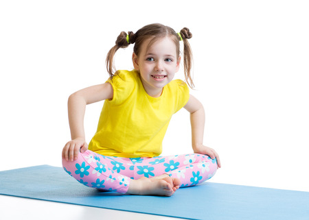 gymnastics: kid girl does gymnastics sitting in butterfly pose isolated on white