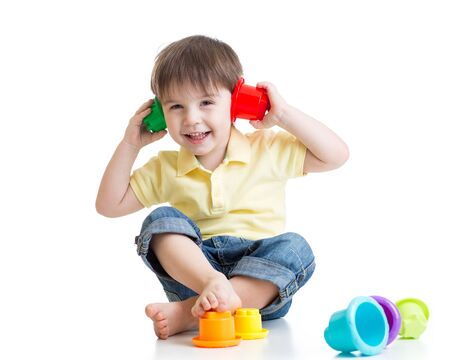Cute little kid is playing with toys while sitting on floor, isolated over white photo