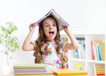 jeune fille souriante de l'enfant avec un livre sur sa tête à l'école primaire