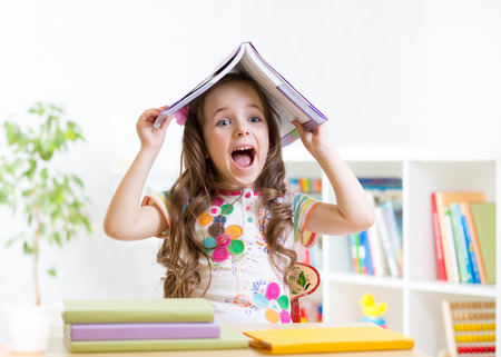 smiling child girl with a book over her head in primary school