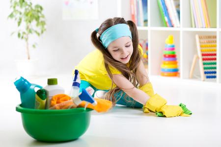 Niño lindo niña limpia un piso en la guardería en el hogar Foto de archivo
