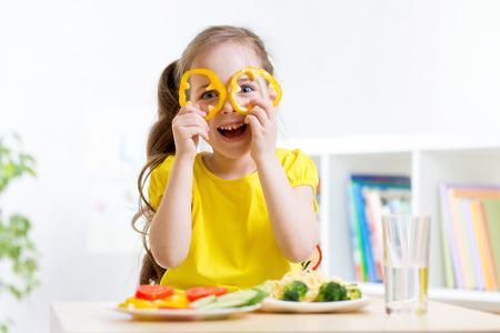 lunch: Chica ni�o come comida vegana que se divierte en el jard�n de infantes Foto de archivo