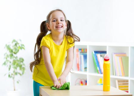 manos limpias: la niña linda que hace la limpieza en la habitación de los niños en el hogar Foto de archivo