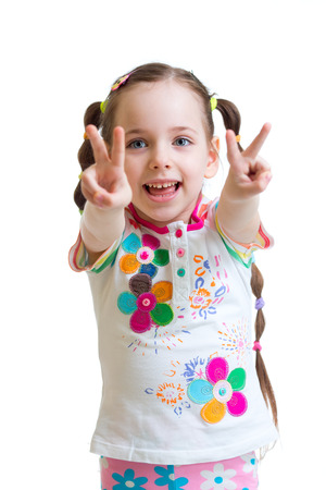 making a face: Portrait of child girl showing victory hand sign on white background