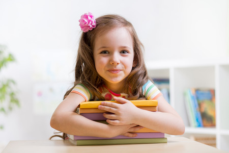 school book: Cute child girl preschooler with books indoor