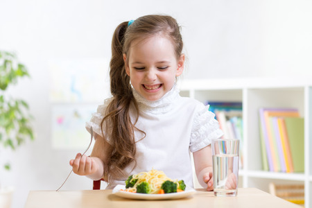 joyful child girl eating healthy food at home or kindergarten