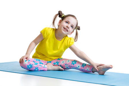 Kid girl doing fitness exercises on mat