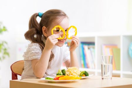 child eats healthy food having fun in kindergarten photo