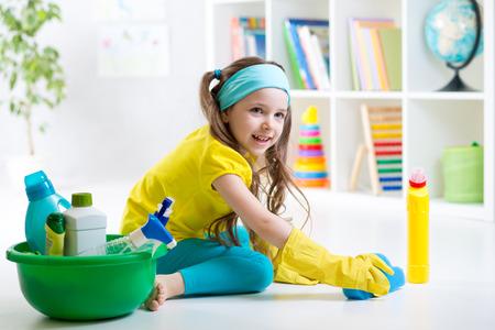 Cute kid little girl cleanses a floor in children room photo