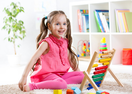happy kid girl playing with abacus toy indoors Stock Photo