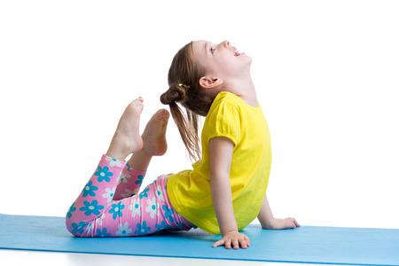 Niño chica haciendo ejercicios de gimnasia en la estera aislada