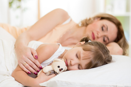 cradling: Child with mom preparing for napping on bed in bedroom