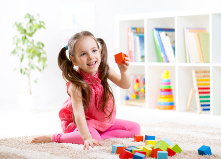 game block: kid child girl playing on floor at nursery or kindergarten