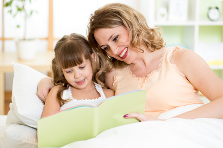 Happy mother and daughter read a book together in bed Stock Photo