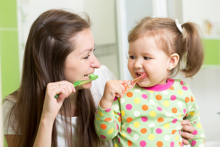 dentists: mother teaching daughter child teeth brushing in bathroom Stock Photo