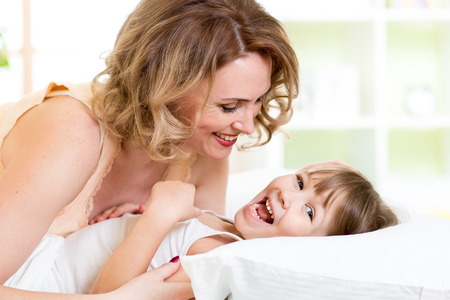family tickle: Happy family - kid with mother play, laugh and tickle in white bed in bedroom Stock Photo