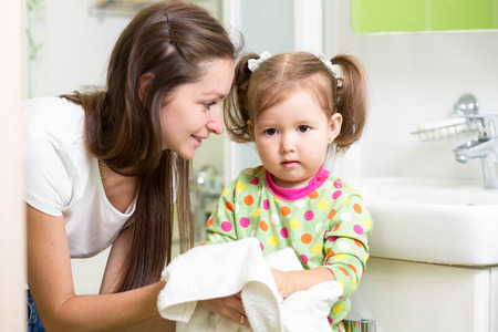 Child girl washing her hands in bathroom. Mom helps her little daughter.
