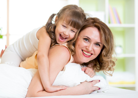 Happy mother and child girl having fun in bedroom photo