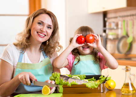 mother and kid have fun cooking in kitchen photo