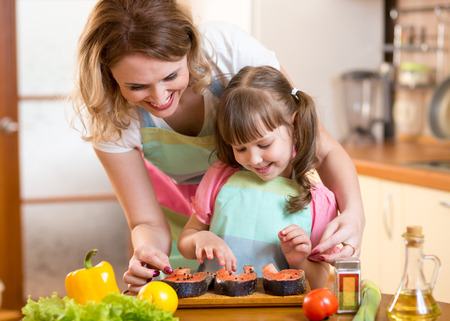 Cute mother with child daughter preparing fish in kitchen