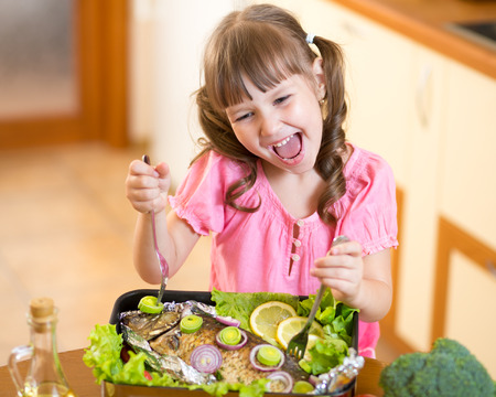 hungry children: Funny child girl and grilled fish at kitchen. Healthy eating seafood.