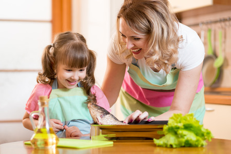 mother cooking: Smiling kid girl with mom cooking fish in domestic kitchen Stock Photo