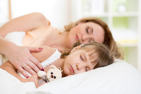 cradling: Child girl with mother preparing for napping on bed in bedroom Stock Photo