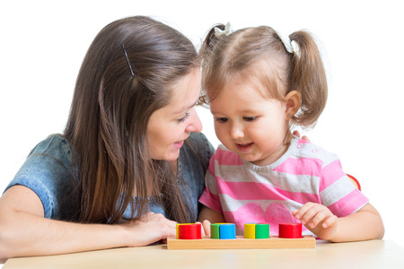 Child girl and mom playing together with puzzle toy photo