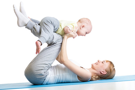 Young woman have fun with baby son doing yoga exercises