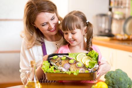 Mère et enfant joyeux regardent plat préparé du poisson dans la cuisine Banque d'images