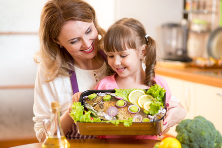 Mother and child jolly look at prepared dish of fish in kitchen Stock Photo