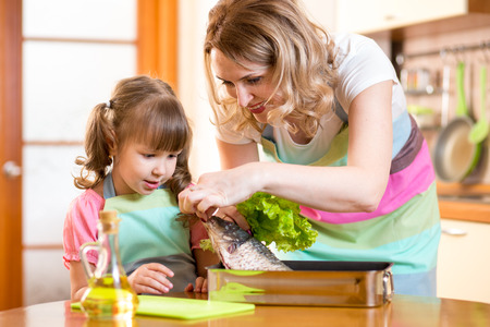 children eating: child girl with mom cooking fish in domestic kitchen Stock Photo