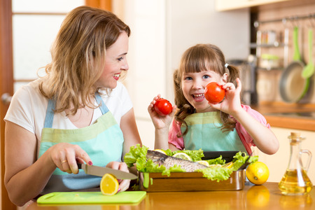 growing up: Mother and child have fun cooking in kitchen at home