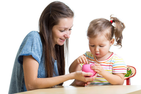 depositing: Mother and daughter child putting coins into piggy bank