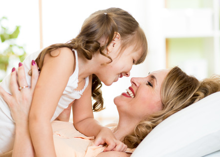 Happy middle-aged mom playing with her kid daughter in bed enjoying  sunny morning in home bedroom Stock Photo
