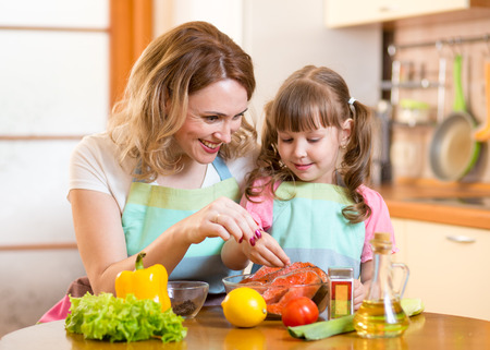 fish oil: Cute middle-aged woman with child daughter preparing fish in kitchen