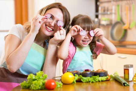 aliments droles: Dr�le m�re et fille jouer avec des l�gumes dans la cuisine, la famille et les aliments sains