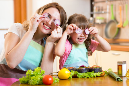 comidas: Madre divertida e hija jugando con verduras en la cocina, la familia y la comida sana