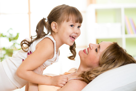 Middle-aged woman together with her daughter child play and laugh in bed enjoying  sunny morning in bedroom photo