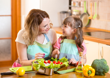 Mother and child have fun cooking in kitchen at home