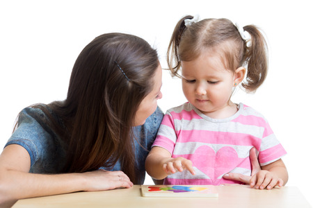 Child girl and mother play together with puzzle toy photo