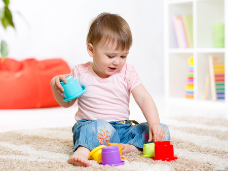 children playing with toys: Kid little girl playing with toys indoors