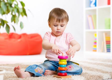 ni�os riendo: Chica de ni�o jugando con juguetes en el interior en el hogar Foto de archivo