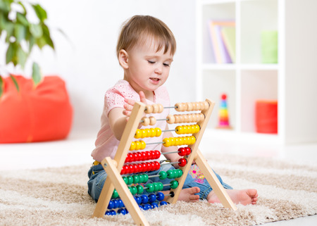home addition: Smiling kid girl playing with counter toy