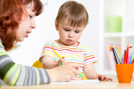 teaching crayons: Mother and daughter child drawing and painting together